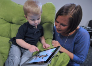 A child reading on his iPad with his mother
