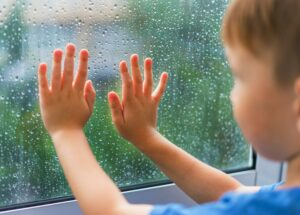 The boy at the rainy window. Children's hands on the wet glass from the rain.